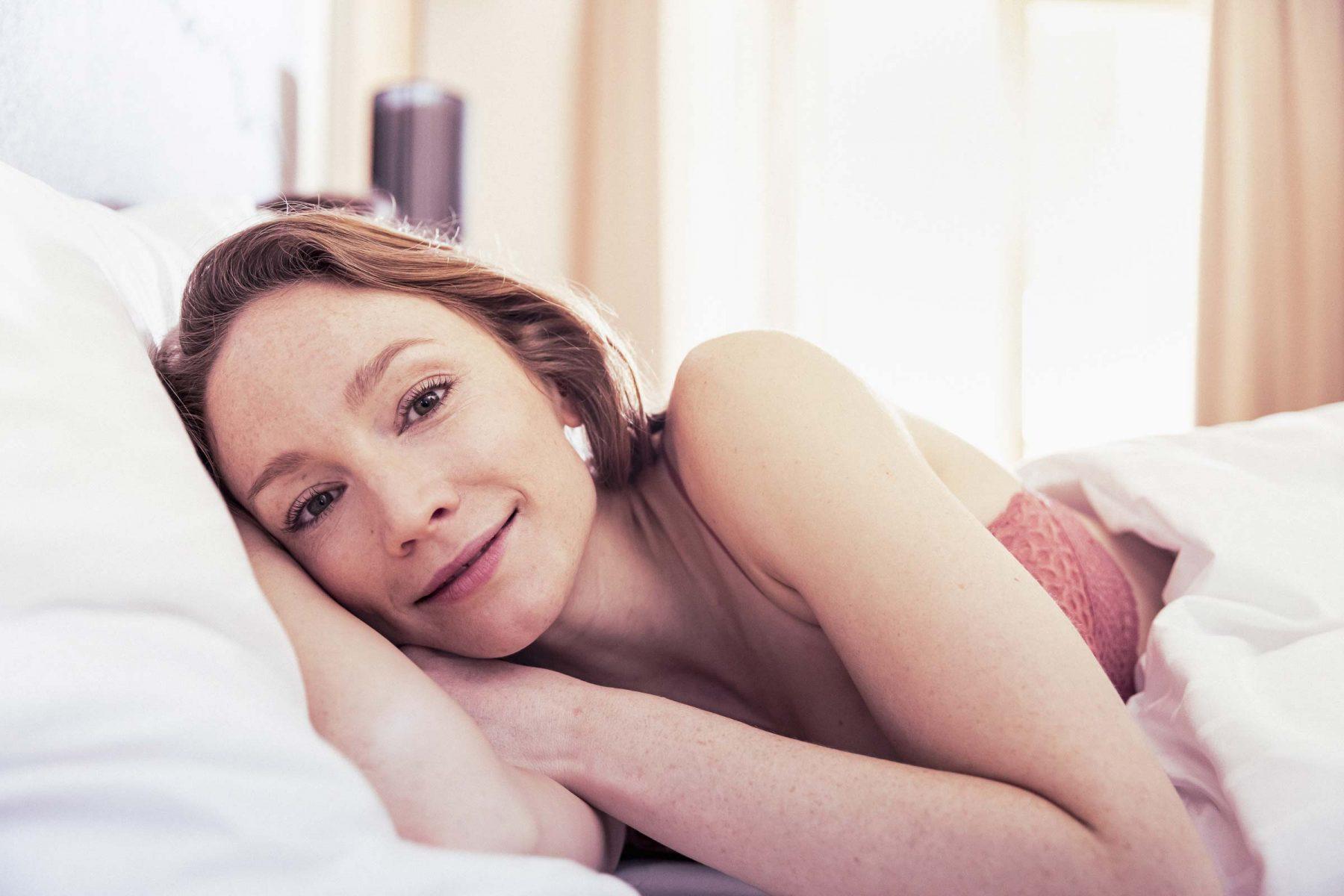 Frau schaut direkt in die Kamera während sie im Bett liegt. Tirol Lodge - Derek Henthorn - Fotograf München