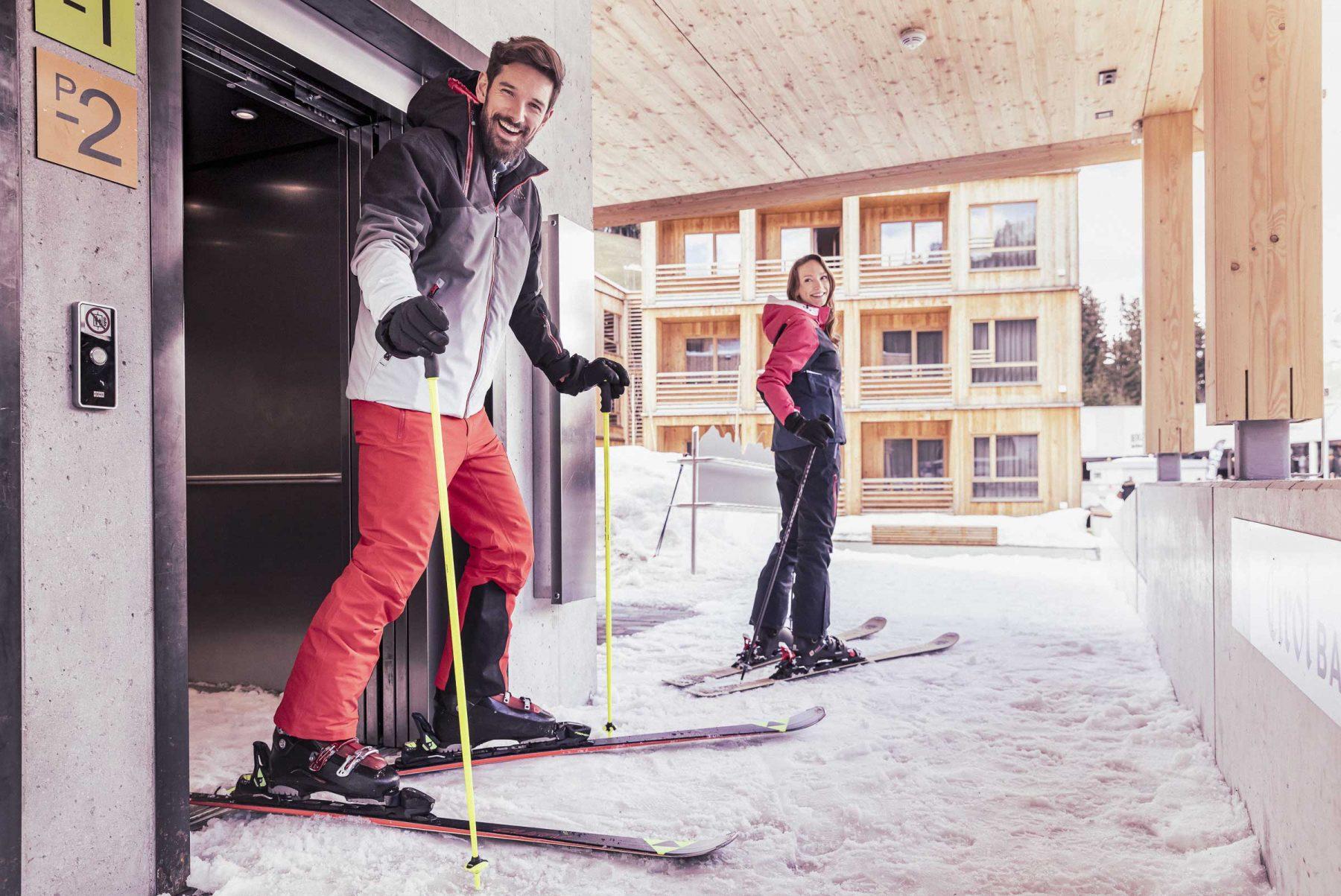Pärchen fährt mit Skiern aus dem Lift direkt auf die Piste. Tirol Lodge - Derek Henthorn - Fotograf München