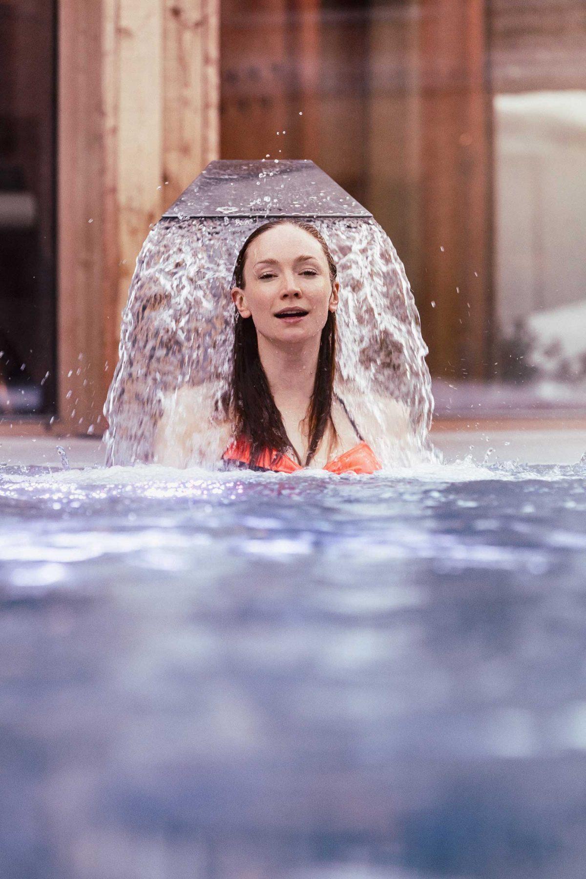 Frau geniesst Wasserspiel im Pool. Tirol Lodge - Derek Henthorn - Fotograf München