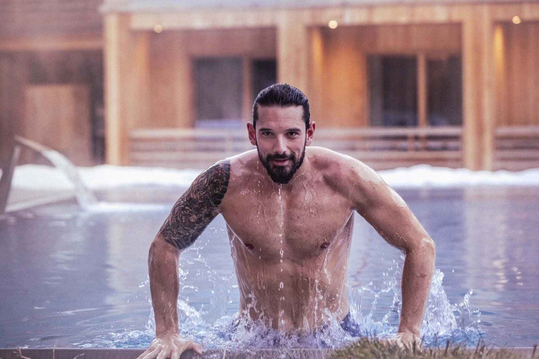 Muskelöser Man presst sich aus dem Pool am Beckenrand. Tirol Lodge - Derek Henthorn - Fotograf München
