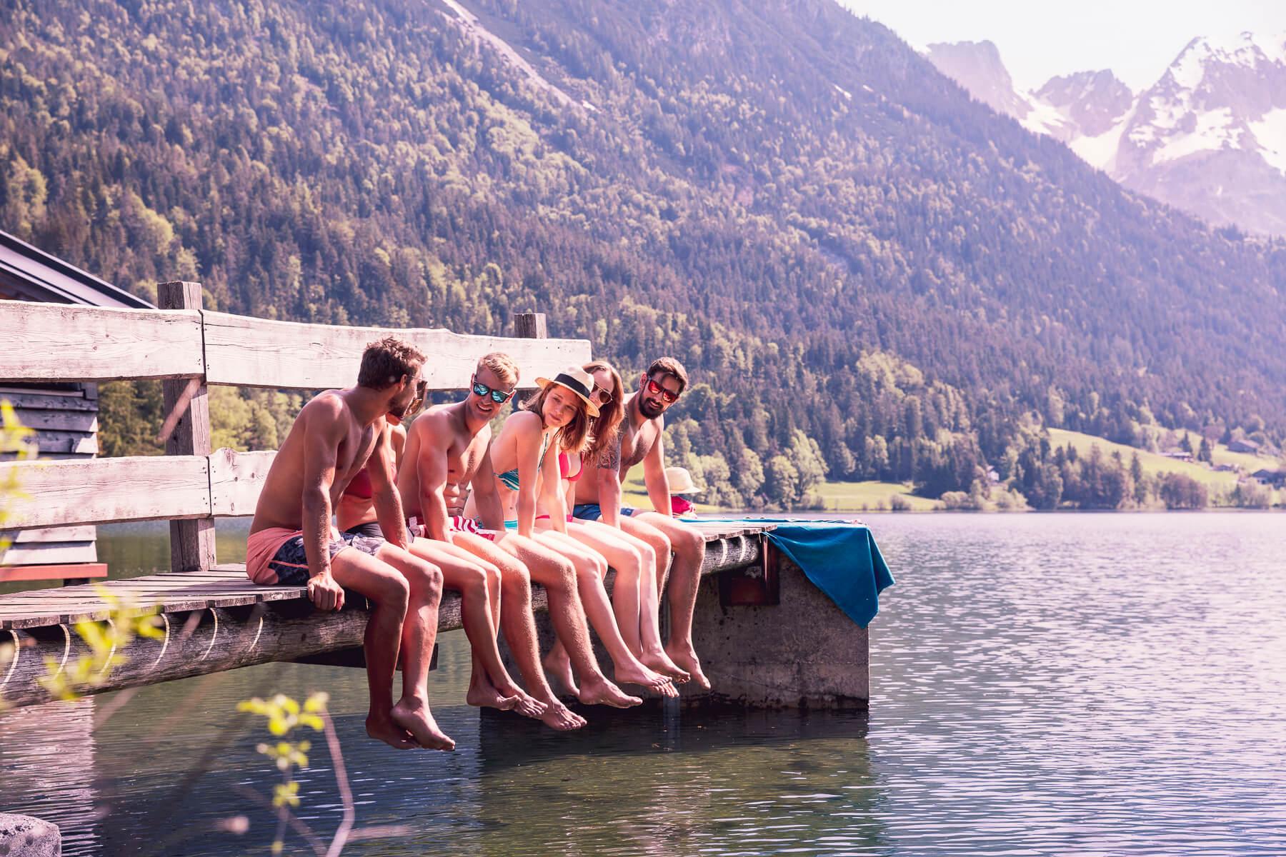 Freunde sitzen auf einem Steg in einem Bergsee. Fotograf Derek Henthorn