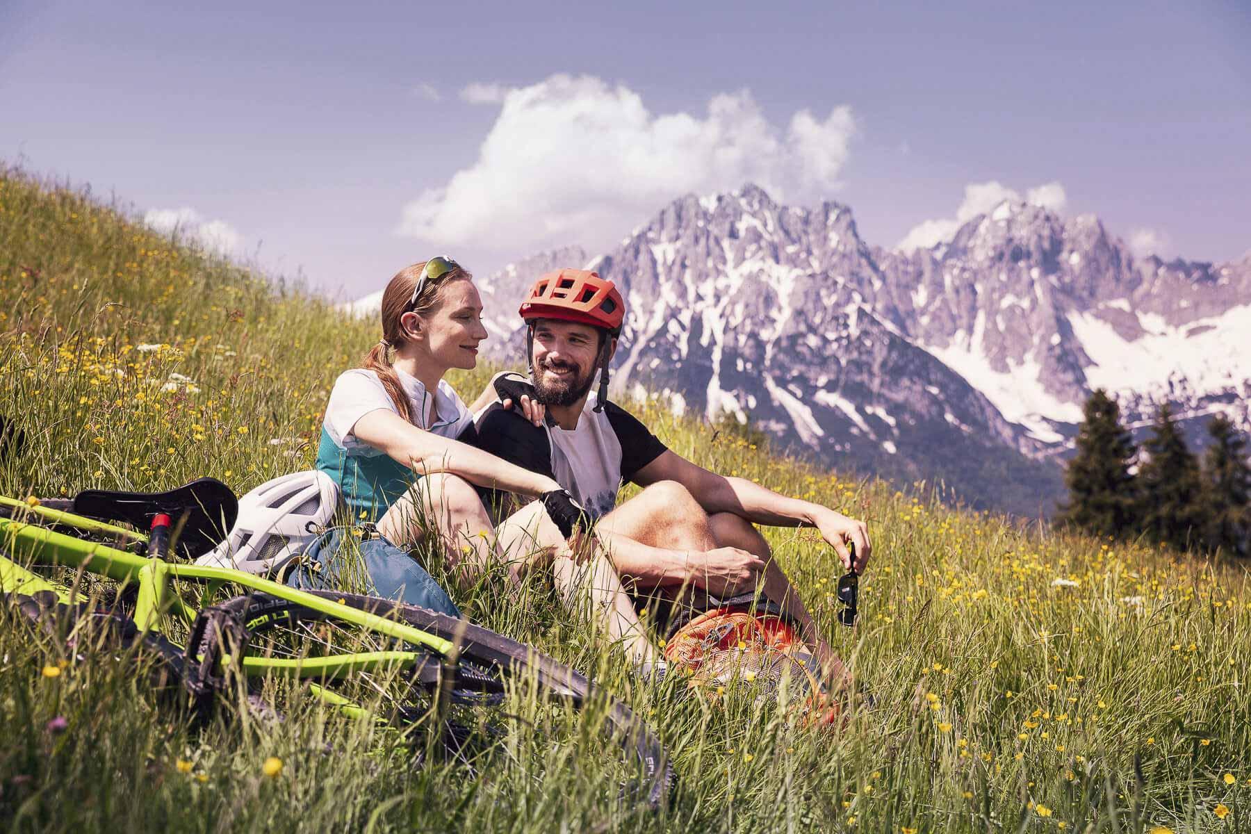 Ein Pärchen entspannt sich beim Mountain Biken in den Bergen. Tirol Lodge - Derek Henthorn - Fotograf München