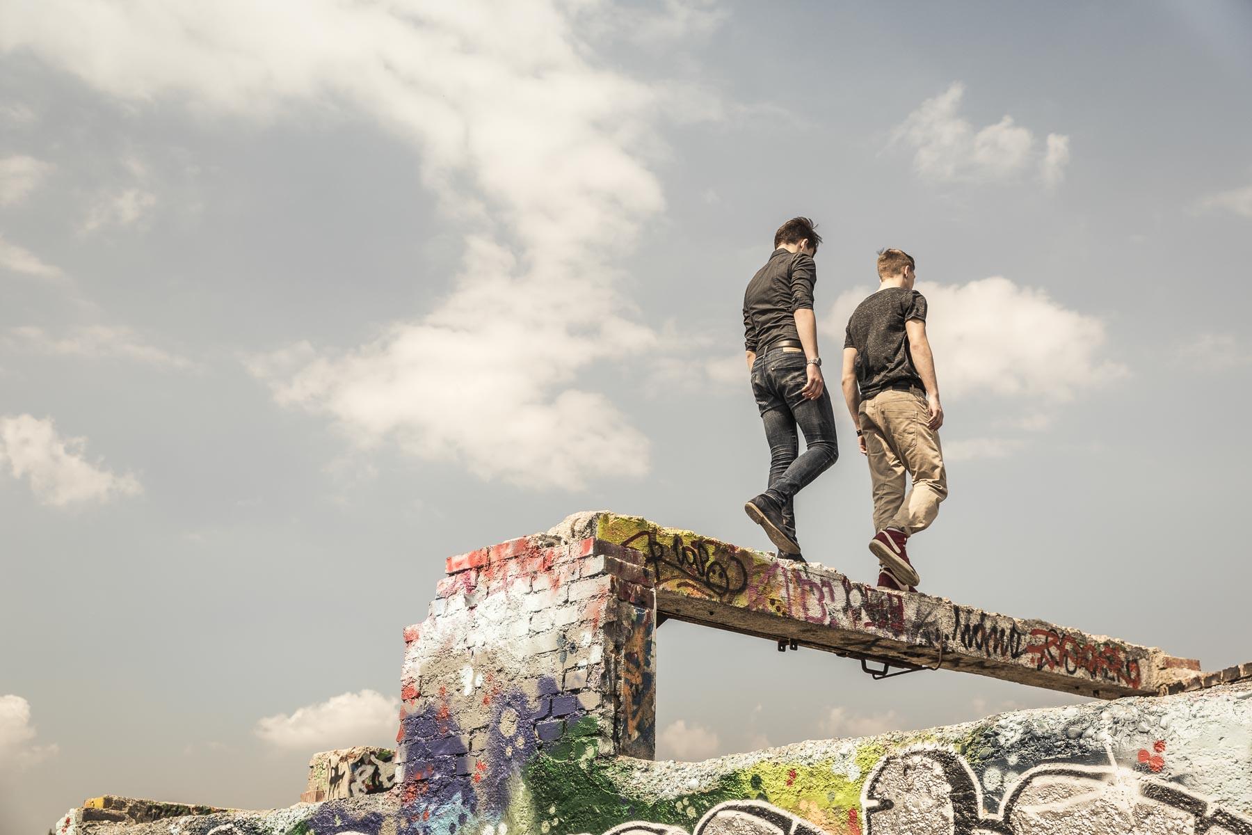 Zwei Teenager laufen auf einem Mauer. Lifestyle - Derek Henthorn - Fotograf München
