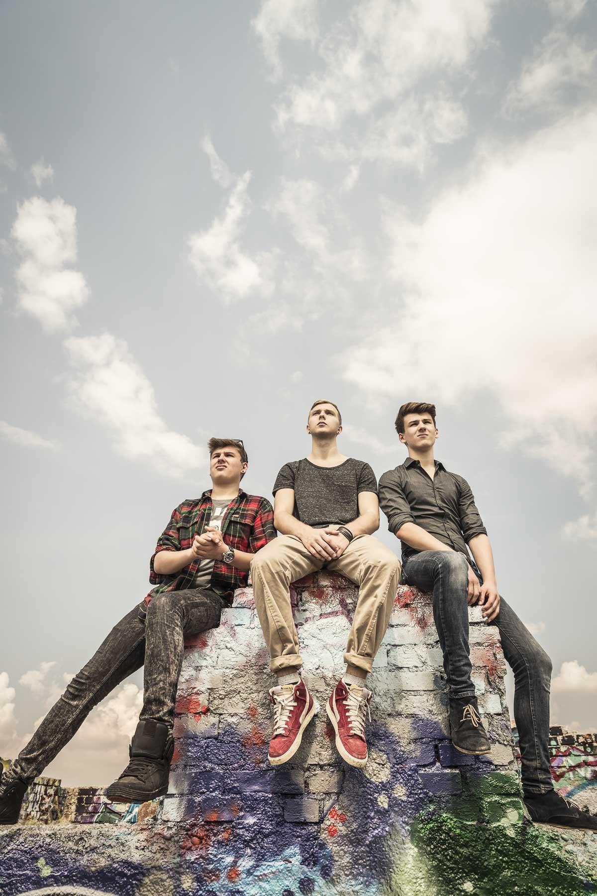 Drei Teenager sitzen heroisch auf einem Mauer. Lifestyle - Derek Henthorn - Fotograf München