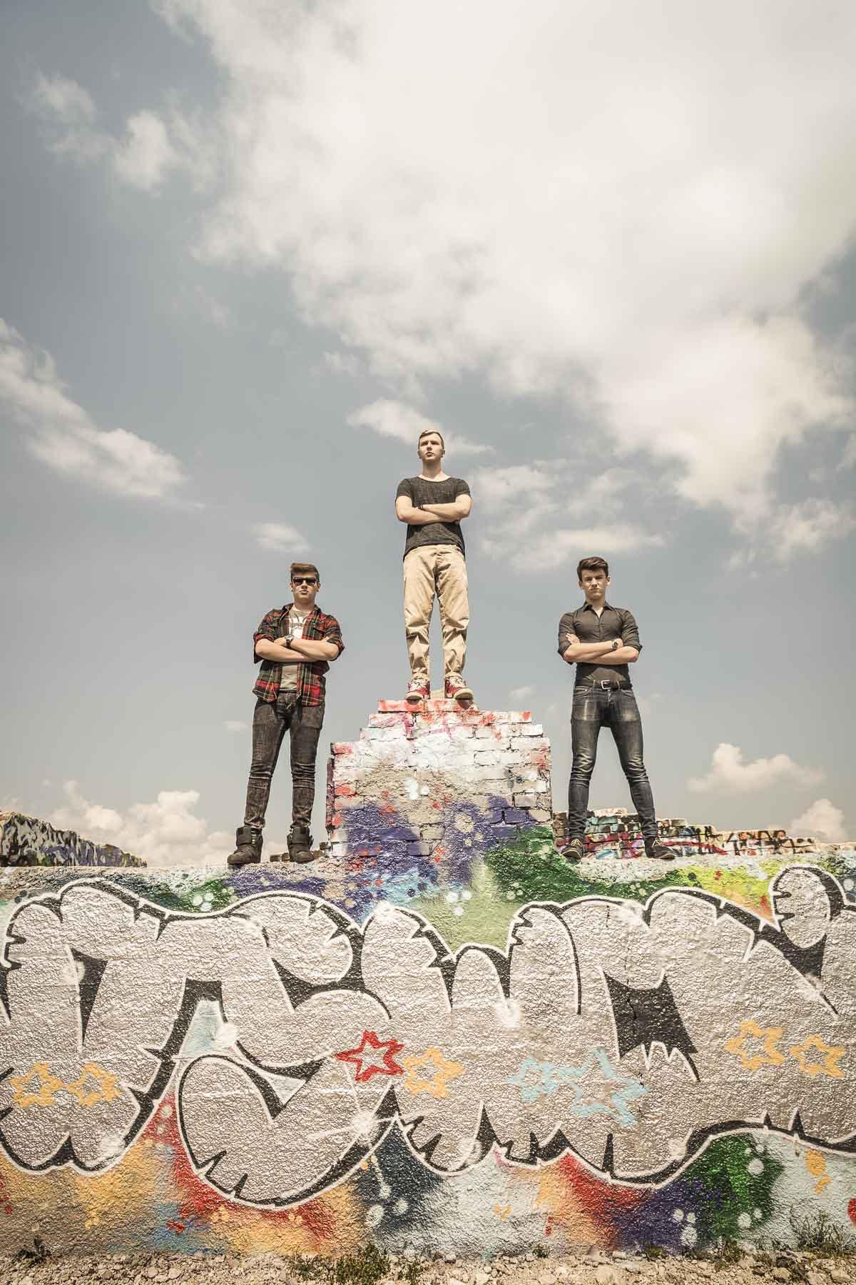 Drei Teenager stehen heroisch auf einem Mauer. Lifestyle - Derek Henthorn - Fotograf München