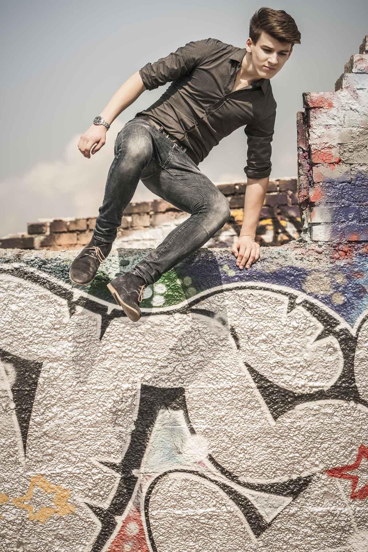Teenager springt von einem Mauer. Lifestyle - Derek Henthorn - Fotograf München